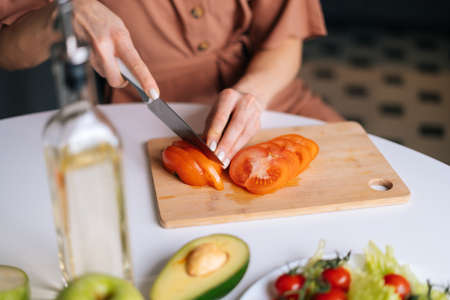 Close-up of hand of woman cutting fresh tomato using kitchen knife on wooden cutting board. Young woman cutting fresh organic tomato with a knife for vegetable salad.