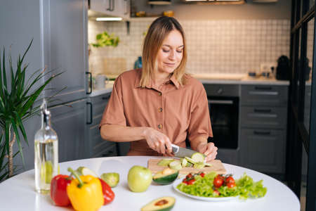 Young smiling vegetarian woman preparing healthy vegan food alone at home. Attractive fit girl prepare healthy dinner, make surprise for husband. Healthy food lifestyle concept.