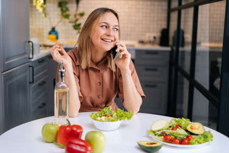 Beautiful young smiling woman talking on phone at the table with vegetables, fruits and salad in kitchen with modern interior. Concept of healthy eating. Stock Photo