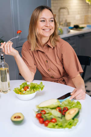 Vegetarian smiling female tasting by spoon fresh vegetable salad while sitting at table in kitchen with modern interior. Concept of healthy eating.
