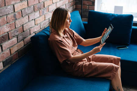 Young happy business woman using digital tablet sitting on cozy couch in living room. Smiling millennial businesswoman designer using digital tablet business apps.