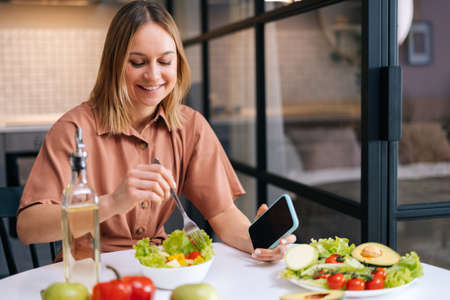 Young smiling woman mixing fresh vegetable salad while sitting at table in kitchen with modern interior, mobile phone on hand. Concept of healthy eating. Stock Photo