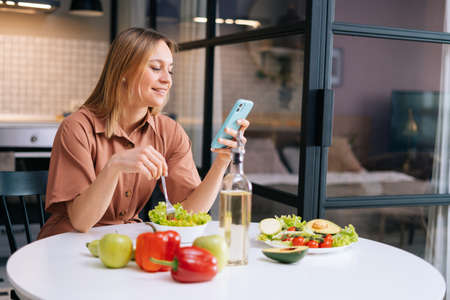 Smiling young woman using her mobile phone while eating salad in cozy wooden kitchen. Concept of healthy eating.