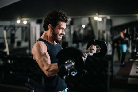 Side view of sportive bearded young man with muscular wiry body wearing sportswear working out with barbell during sport workout training in modern dark gym. Concept of healthy lifestyle. Stock Photo