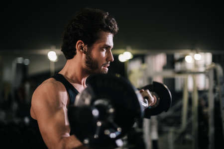 Handsome bearded young man with muscular wiry body wearing sportswear working out with barbell during sport workout training in modern dark gym. Concept of healthy lifestyle.