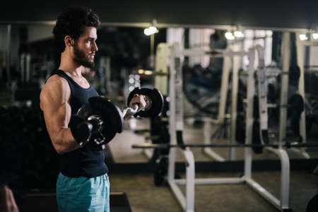 Strong bearded young man with muscular wiry body wearing sportswear working out with barbell during sport workout training in modern dark gym. Concept of healthy lifestyle.