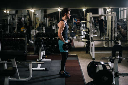 Sportive bearded young man with muscular wiry body wearing sportswear holding barbell during sport workout training in modern dark gym. Concept of healthy lifestyle.