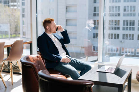 Bearded young businessman wearing fashion suit is talking on mobile phone in modern office room at the desk in modern office on background of large window, laptop on table. Concept of office working. Фото со стока