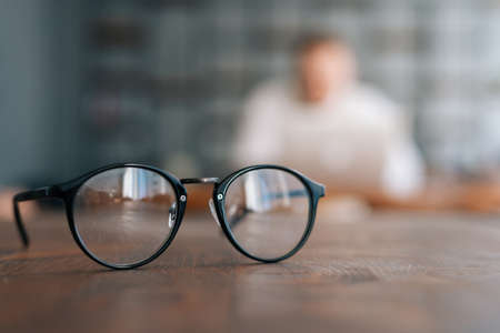 Stylish glasses on the wooden table in modern office room. Blurred silhouette of unrecognizable man on background.