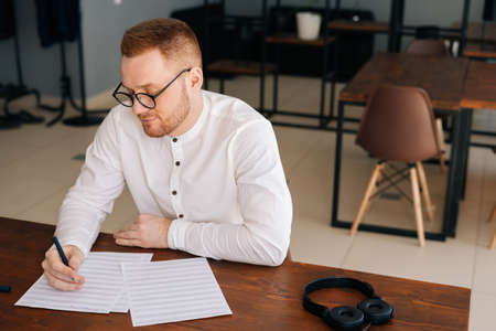 Talented young composer wearing stylish eyeglasses writing musical notes with pen on paper sheet music sitting at the wooden desk in modern room in office or home, headphones on table Stock Photo