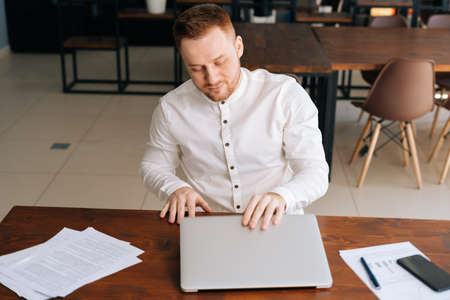 Professional young businessman wearing fashion casual clothing is closing on laptop lid at the table in modern office room. Concept of office working.