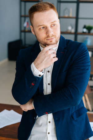 Close-up portrait of Thoughtful young business man wearing fashion casual clothing is standing in modern office room near wooden desk. Concept of office working. Stock Photo