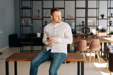 Caucasian young businessman wearing fashion casual clothing is using mobile phone in modern office room sitting on wooden desk, looking away. Concept of office working. Stock Photo