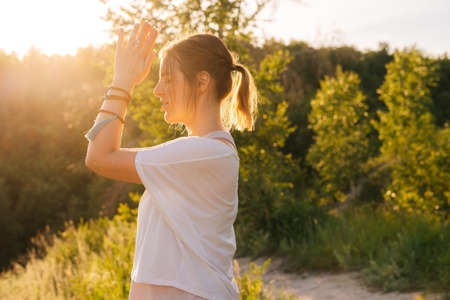 Side view of happy meditating woman raising hands in Namaste pose background of bright sun rays. Beautiful girl meditating, doing breathing exercising. Concept of practicing yoga alone outdoor. Reklamní fotografie