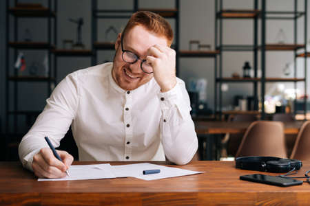 Laughing happy composer wearing stylish eyeglasses is writing note of song with pen on paper sheet music sitting at the wooden desk in modern room.