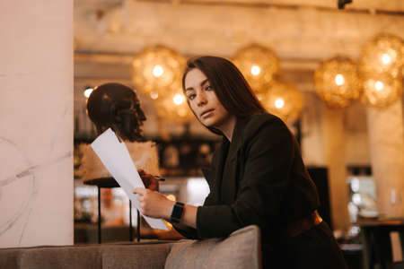 Successful young business woman wearing stylish formal clothes in modern luxury restaurant holding paper documents in her hands. Business lady lady in suit posing in cafe, looking at camera. Imagens