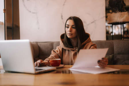 Attractive young businesswoman is typing on laptop computer and working with paper document in cozy cafe. Girl is taking notes in documents and working on laptop. Cup of coffee on the table. Imagens