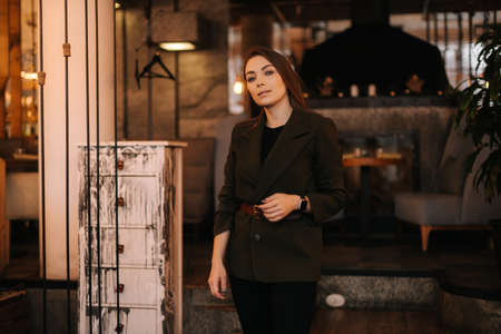 Serious lady posing background of entrance at dark office building. Young businesswoman standing outdoors. Imagens