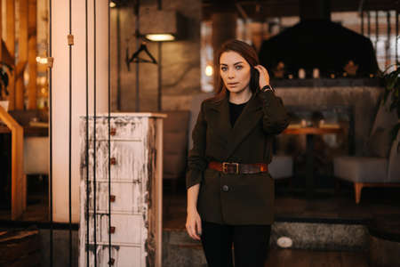 Attractive business lady posing background of entrance at dark office building. Young businesswoman standing outdoors.