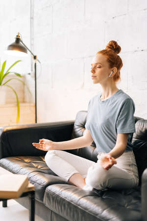 Loving redhead young woman meditating and relaxing in lotus pose while sitting on soft couch. Business lady taking break from work at computer and documents