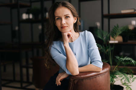 Serious young businesswoman wearing stylish light blue dress sitting at the chair in office with modern interior, looking at the camera. Portrait of charming business lady.