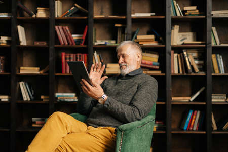Happy cheerful mature adult male having online video chat by digital tablet. Older man says goodbye to friend, waving goodbye gesture at home on background of bookshelves in cozy room.