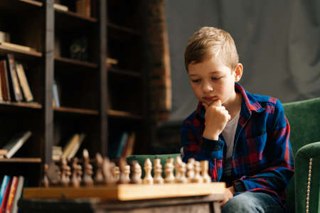 Close-up portrait of clever pensive little boy thinking about next move over the chessboard holding hand near chin sitting at desk in room with an authentic interior. Preschool-aged boy playing chess.