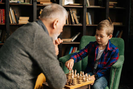 Back view of pensive beard grandfather playing chess with grandson, thinking about next step in chess game sitting at chessboard in front of child. Grandchild playing chess with grandparent.