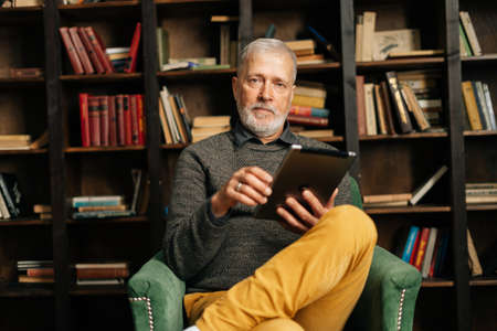 Portrait of bearded mature adult male browsing internet on digital tablet, sitting at home on background of bookshelves in cozy dark room with an authentic aristocratic interior, lookig at the camera. Archivio Fotografico