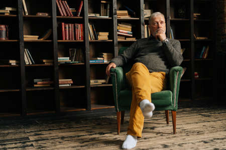 Worried bearded gray-haired elderly man thoughtfully holding hand with watch near chin, sitting at home on background of bookshelves in cozy room with an aristocratic interior, shooting from below. Archivio Fotografico