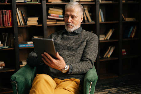 Gray-haired mature adult male is speaking on video call with friend client colleague family sitting at table at home on background of bookshelves in cozy room with an authentic aristocratic interior.