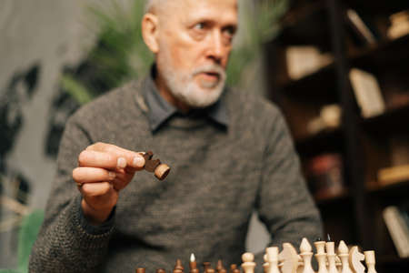 Caucasian mature adult bearded gray-haired man making move at chess game, sitting at home on background of bookshelves in cozy dark room with an authentic aristocratic interior. focused on foreground.