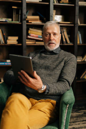 Portrait of bearded gray-haired mature adult male using digital tablet sitting at table at home on background of bookshelves in cozy room with an authentic aristocratic interior, looking at camera.