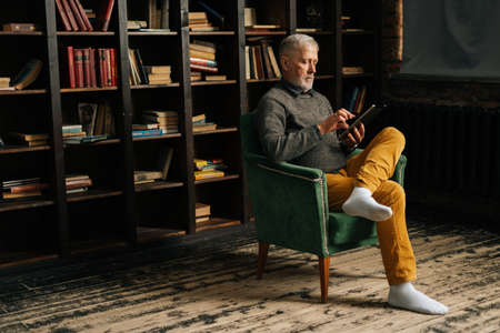 Side view of senior adult male browsing internet using digital tablet, sitting at home in armchair on background of bookshelves in cozy dark room with an authentic aristocratic interior. Archivio Fotografico