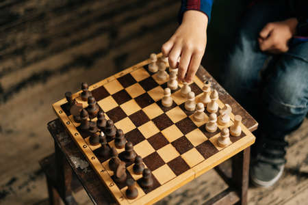 Close-up of hand of unrecognizable child making his move in chess game. Kid boy playing chess, leisure activity, having fun. Archivio Fotografico