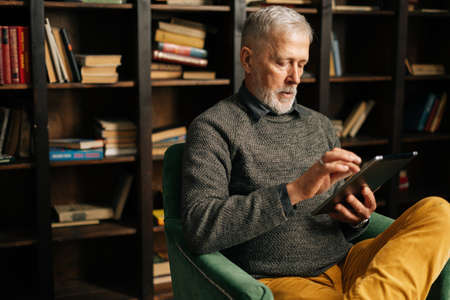 Close-up face of bearded gray-haired mature adult male having break with digital tablet, sitting at home on background of bookshelves in cozy living room with authentic aristocratic interior.
