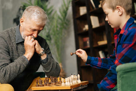 Boy playing chess with grandfather in chess game sitting at chessboard. Pensive beard grandfather thinking about next step in chess game. Archivio Fotografico