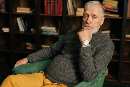 Portrait of bearded gray-haired elderly man thoughtfully holding hand with watch near chin, sitting at home on background of bookshelves in cozy dark room with an aristocratic interior. Archivio Fotografico
