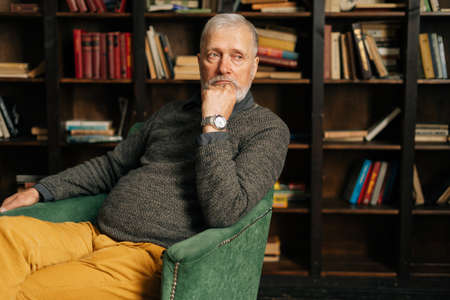 Portrait of pensive bearded gray-haired senior male, thoughtfully holding fist hand near chin, sitting at home on background of bookshelves in cozy dark room with an authentic aristocratic interior.