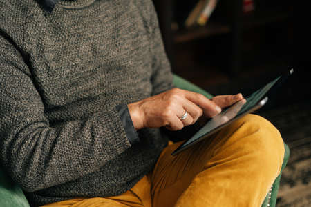 Close-up of hands of unrecognizable senior adult male browsing internet content using digital tablet, sitting at home in armchair in cozy living library room with an authentic aristocratic interior.