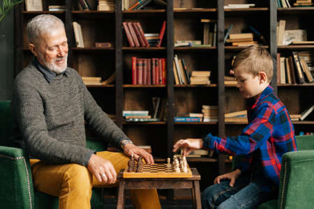 Smiling happy old senior grandfather and grandson are playing chess sitting at desk at home on background of bookshelves in cozy dark room with an authentic aristocratic interior. Archivio Fotografico