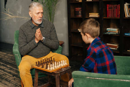 Focused mature adult grandfather explaining rules of chess game to grandchild at home on background of bookshelves in cozy dark room with an authentic aristocratic interior.