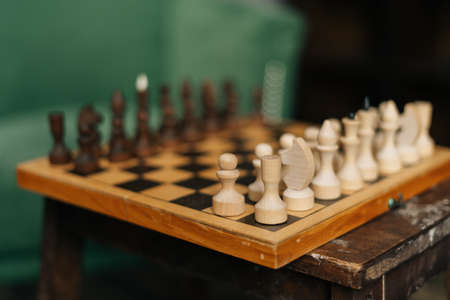 Side view of chessboard with placed chess pieces on black old vintage table, focus on foreground. End of preparation for an intellectual game in a warm home atmosphere.