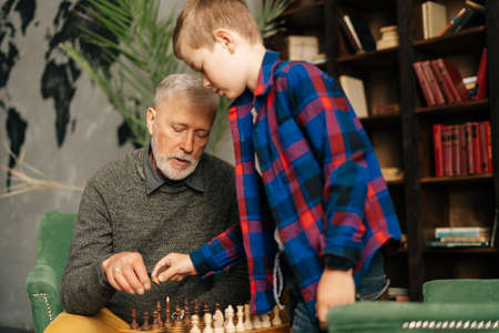Grandfather and grandson setting wooden chess figures on chessboard preparing to play sitting at desk at home on background of bookshelves in cozy dark room with an authentic aristocratic interior.