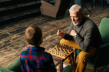 Top view of aged-male grandfather playing chess with grandson sitting at desk in cozy dark living room with an authentic aristocratic interior. Grandpa tells little kid boy about the tactics of game.