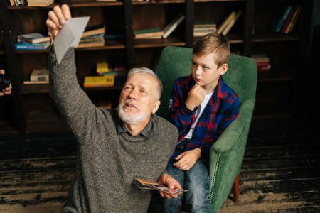 Caucasian cheerful bearded gray-haired grandfather with his grandson enjoy memories watching family photo album sitting on armchair and floor at home in room with an authentic aristocratic interior.