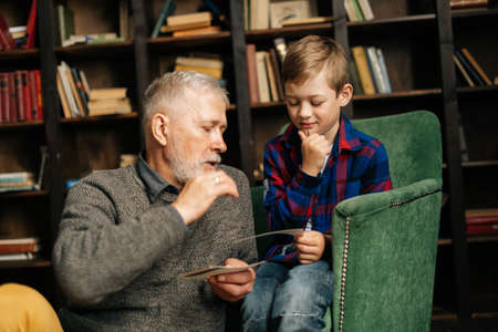 Close-up portrait of grandpa talking with little grandson, having fun looking at old photo album, enjoying memories watching family photo album at home in cozy room background on bookshelves