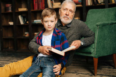 Portrait of child boy sitting with his grandfather and reading an interesting book together. Bearded gray-haired grandpa reading book for grandson, looking at the camera. Archivio Fotografico