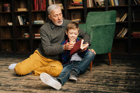 Mature grandfather and little grandson reading interesting book together sitting on floor on home library room. Bearded gray-haired grandpa reading book for grandson. Archivio Fotografico