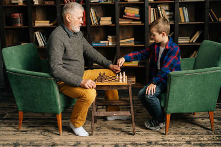 Side view of bearded mature adult grandfather and grandson playing chess sitting at table at home on background of bookshelves in cozy dark room with an authentic aristocratic interior.